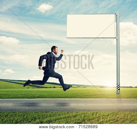 successful businessman running on the road against empty billboard and green field