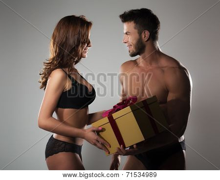 Man giving gift to woman. Beautiful young couple