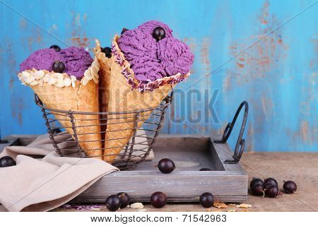 Tasty ice cream with berries in waffle cones on blue wooden background