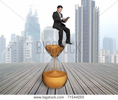 Businessman Using Smart Pad Sitting On Hour Glass