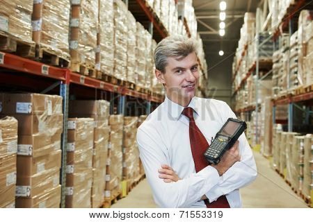 smiling manager in warehouse with bar code scanner