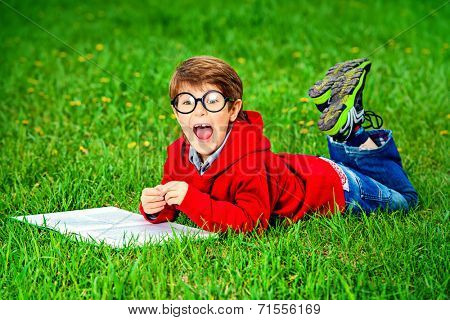Cute 7 years old boy lying on a grass with a book and shouting.