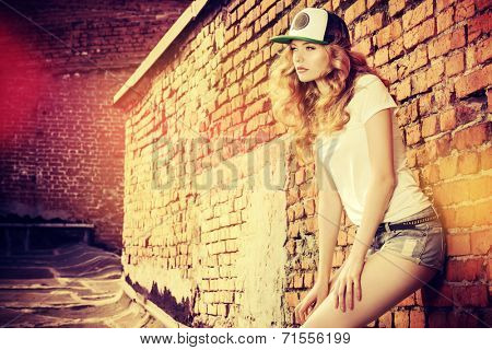 Beautiful modern girl near the brickwall in the rays of the evening sun. Youth style. Fashion shot.