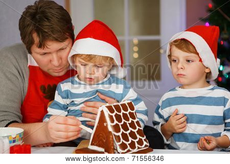 Father And Two Little Sons Preparing A Gingerbread Cookie House