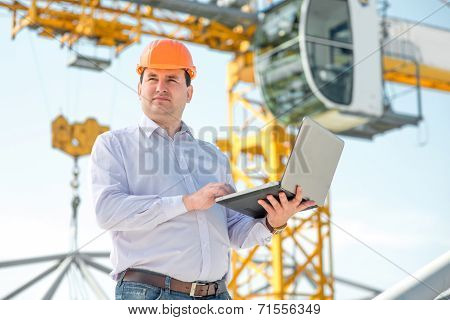 A Foreman With Laptop At The Construction Supervising The Project.