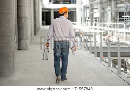 A Foreman With Drawings And Case Supervising The Project At The Construction.