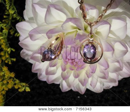 Pendant and a ring with alexandrites against the backdrop of white-lavender dahlia