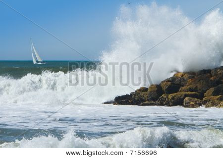 Ocean Surf Breaking Over Jetty With Sailboat