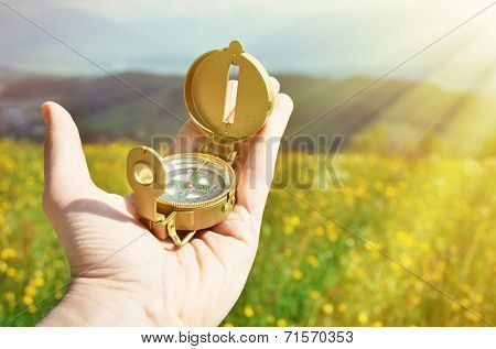 Compass in the hand against Alpine meadow