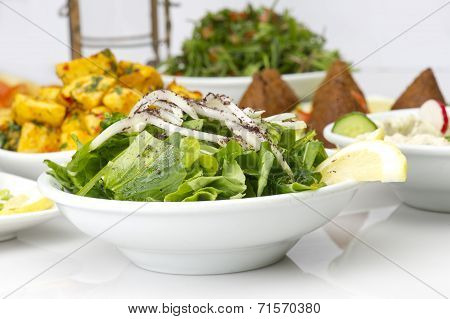 Lebanese food of Arugula Salad, Kibbeh, and Potato cubes