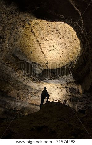 Man exploring big cave underground