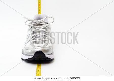 Running shoe and yellow centimeter
