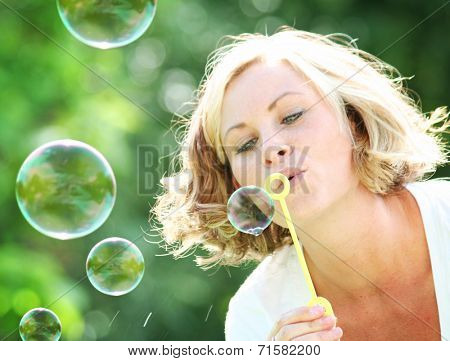 a beautiful woman blowing bubbles outside in a park or backyard on a warm sunny summer day