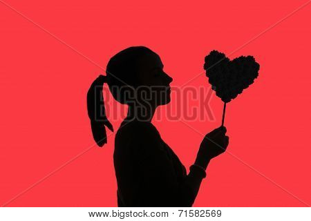 Silhouette Of Teenage Girl With Ponytail, Holding Flower Heart In The Hand, Red Background