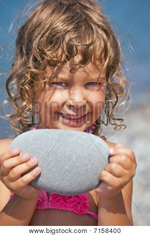 Smiling Pretty Little Girl Holds In Hands Pebble On Seacoast