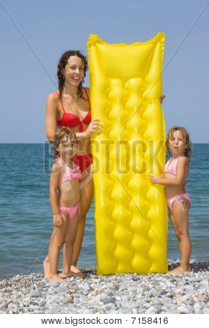 Young Woman And Two Little Girls Standing On Beach