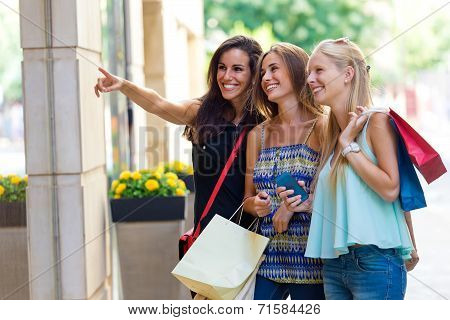 Group Of Beautiful Girls Looking At The Shop Window.