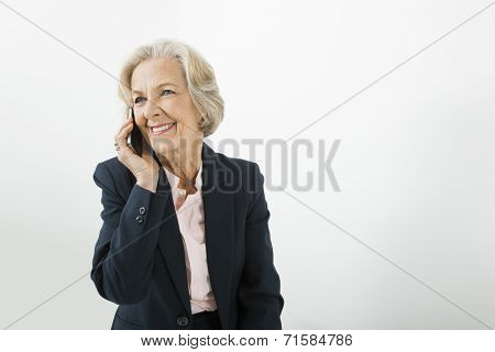 Senior businesswoman using cell phone in office