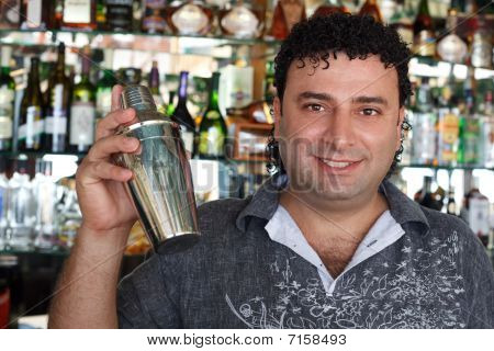 Barman with shaker behind bar rack. Smiling man against shelves with bottles.