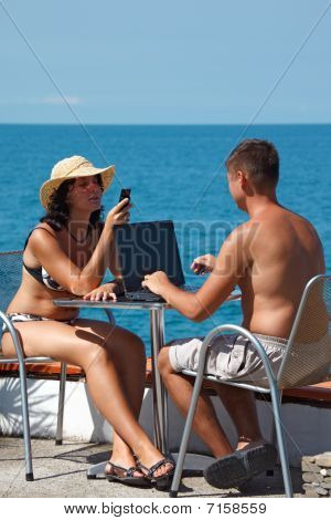 Man and woman sitting at table under open sky on background of sea. Man works for laptop.