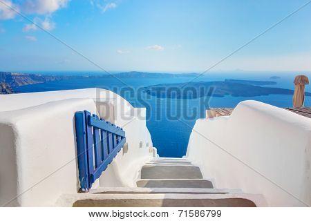 Open blue door with Aegean sea view, Caldera and volcano island. Oia town on Santorini, Greece.