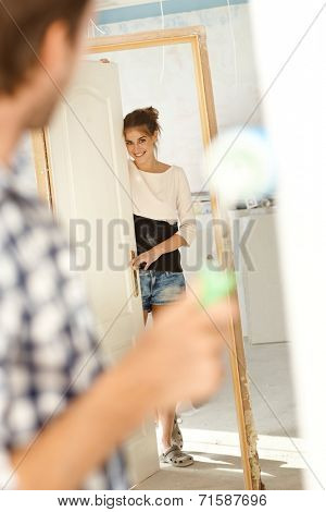 Attractive young woman looking at man in new house under construction. Woman looking through door frame, man painting wall.