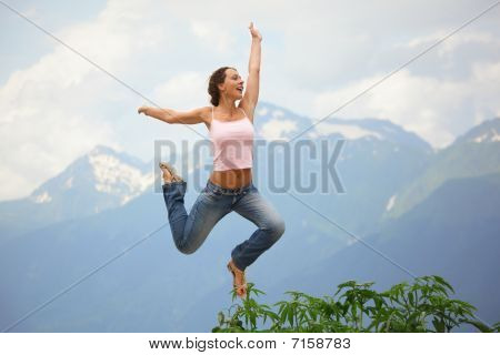 beautiful joyful woman is jumping. mountains behind her.