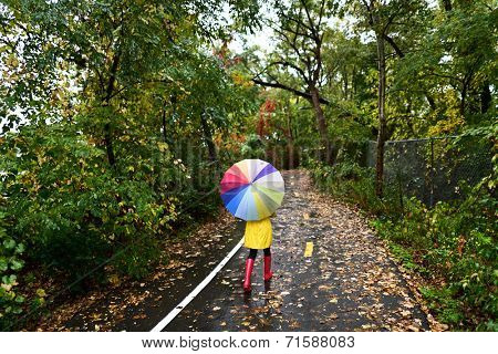 Autumn / fall concept - woman walking in forest with umbrella in rain. Girl enjoying rainy fall day.