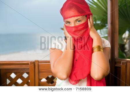 Young Woman In Yashmak Sitting  In An Arbour On Seacoast