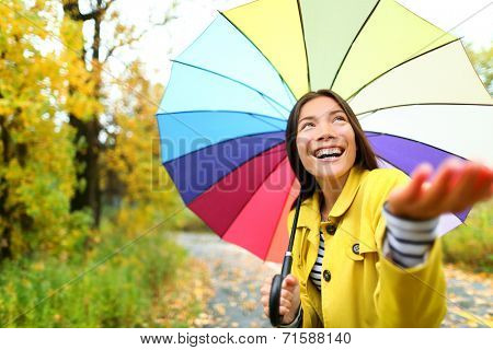 Autumn / fall woman happy in rain with umbrella. Female model looking up at clearing sky joyful on rainy fall day wearing yellow raincoat outside in nature forest by lake. Multi-ethnic Asian girl.