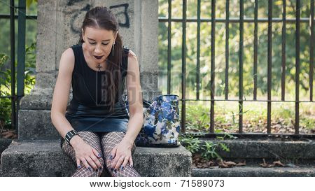 Pretty Goth Girl Sitting In A City Park