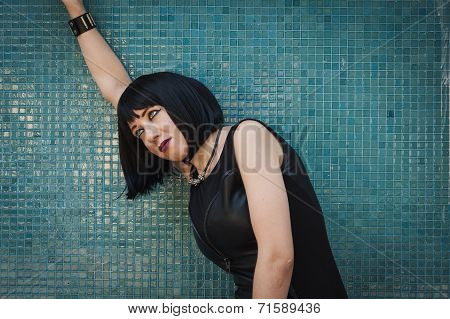 Pretty Goth Girl Posing Against A Blue Wall