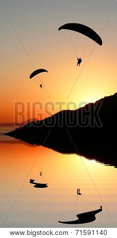 Silhouette Paragliders In Coastal Sunset Landscape