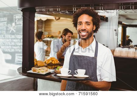 Handsome waiter smiling at camera holding tray at the coffee shop