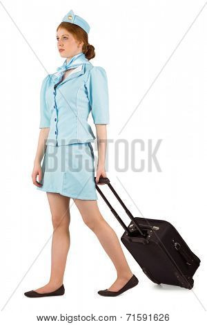 Pretty air hostess pulling suitcase on white background