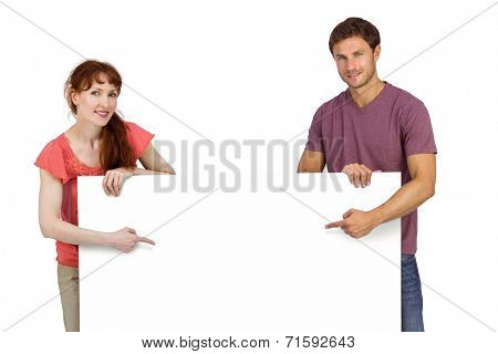Couple looking at the camera on white background while pointing