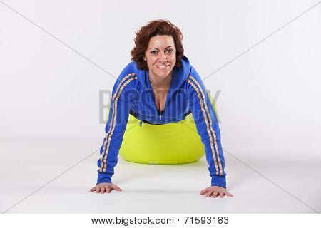 Happy mature woman exercising with a yellow pilate ball (isolated on white)