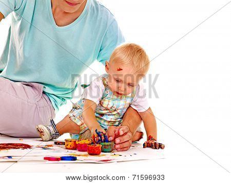 Little boy painting by finger paint.