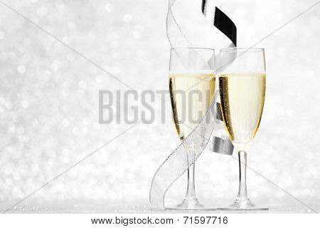 Glasses of champagne and silver ribbons on glitter background