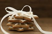 stock photo of ginger bread  - Ginger Bread Cookies with white Ribbon and Bow on Wood with Copy Space - JPG