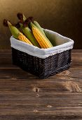 foto of corn-silk  - Corn cobs on basket with a rustic wood planks background - JPG