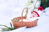 stock photo of christmas baby  - Funny happy baby boy wearing a warm snow suit and a red knitted snowman hat laying in a basket as a Christmas present in a beautiful winter park - JPG