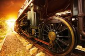 foto of suspension  - iron wheels of stream engine locomotive train on railways track perspective to golden light forward use for old and classic period land transport and retro vintage style background - JPG