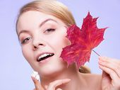 picture of capillary  - Face of young woman with leaf as symbol of red capillary skin on violet. Girl taking care of her dry complexion applying moisturizing cream.  ** Note: Soft Focus at 100%, best at smaller sizes - JPG
