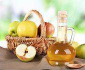 stock photo of cider apples  - Apple cider vinegar in glass bottle and ripe fresh apples - JPG