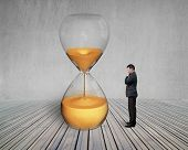 stock photo of waste management  - standing manager looking the hourglass with concrete wall and wooden floor - JPG