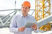 picture of supervision  - A foreman with digital tablet at the construction supervising the project - JPG