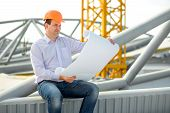 image of supervision  - A foreman with drawings supervising the project at the construction - JPG