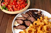 foto of flank steak  - Flank steak with fries onion rings and salad - JPG