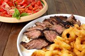 stock photo of flank steak  - Flank steak with fries onion rings and salad - JPG